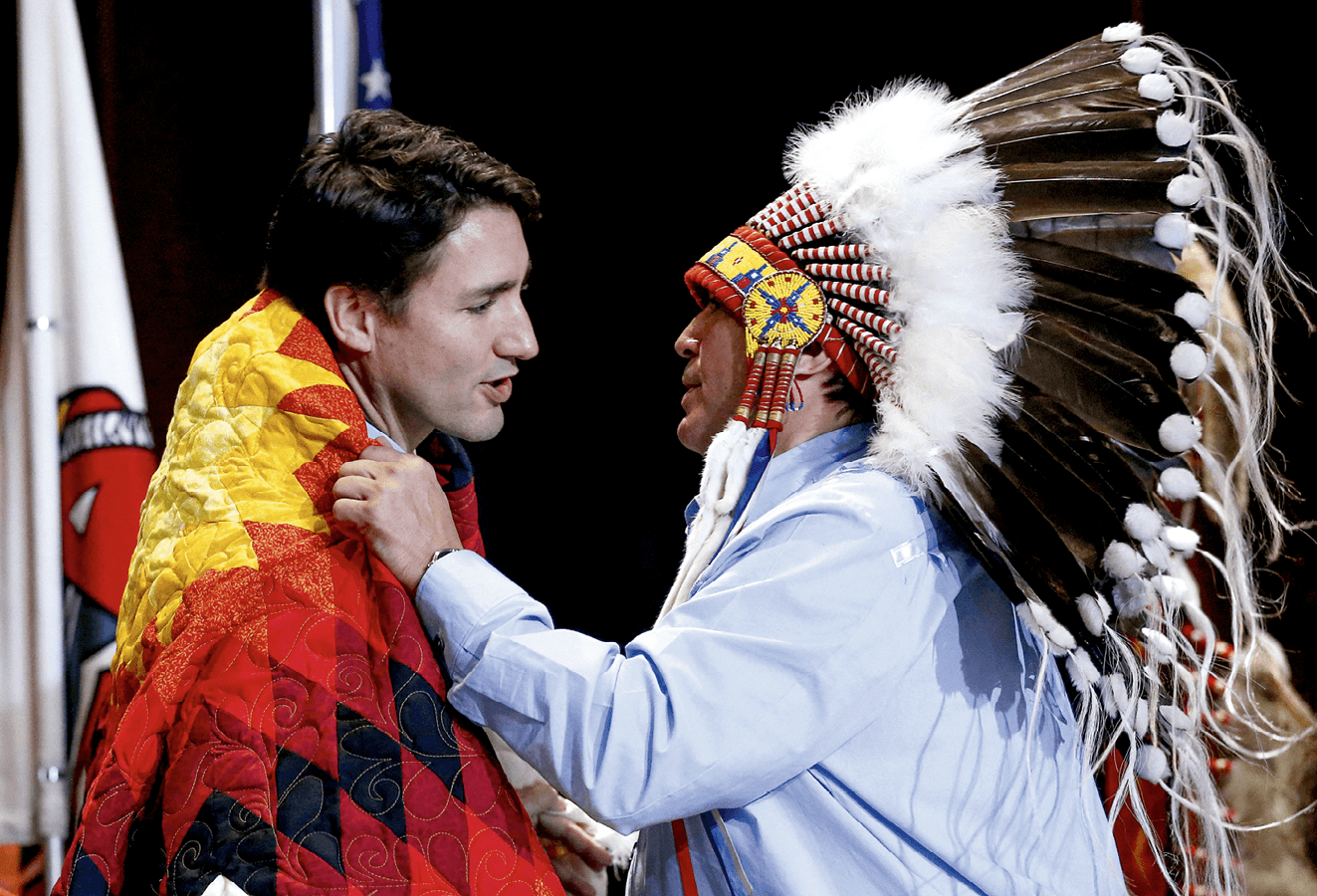 National Chief Perry Bellegarde adjusts a blanket presented to Prime Minister Justin Trudeau during the Assembly of First Nations Special Chiefs Assembly in Gatineau
