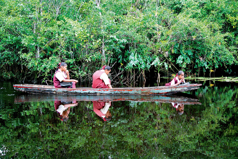 Girls wearing school uniforms in a boat on their way home from school, Guyana