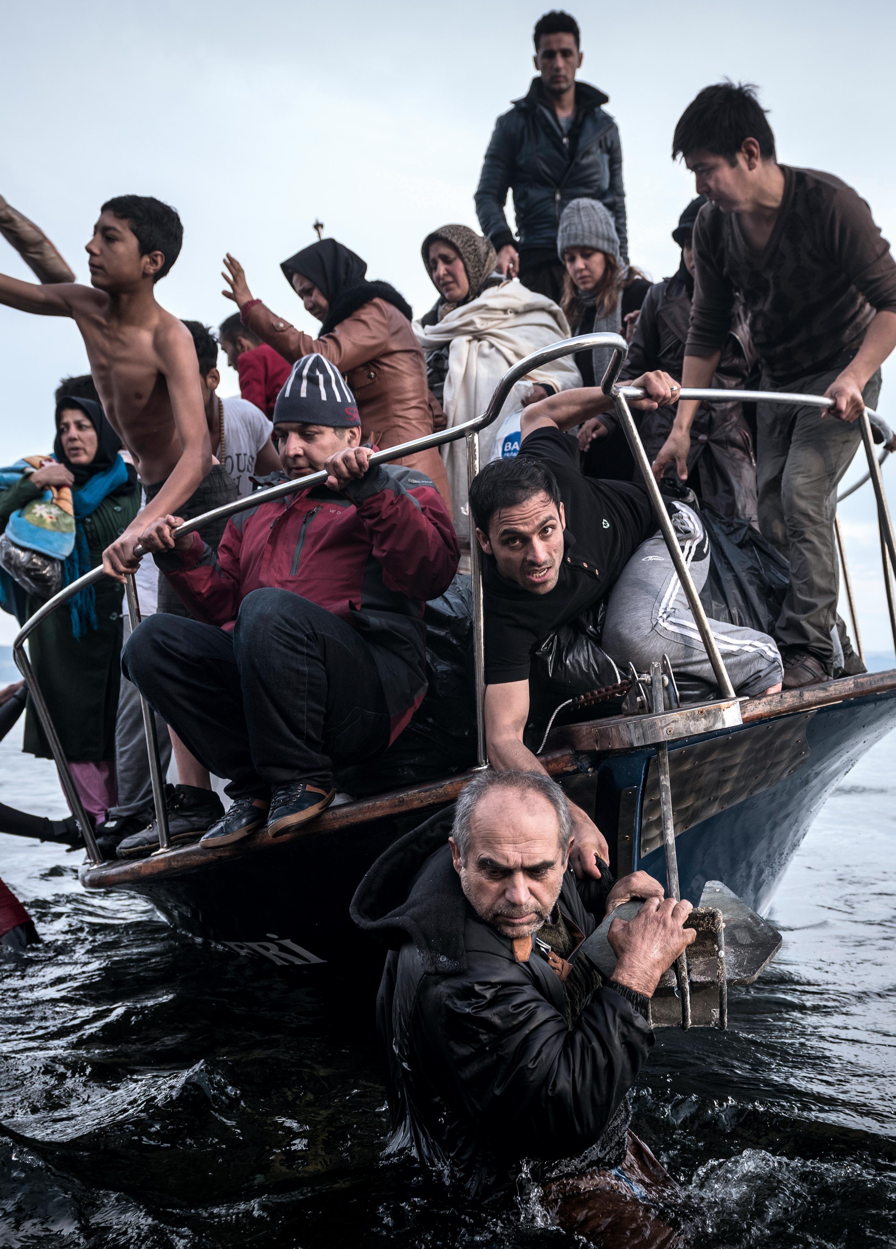 Migrants arrive by a Turkish boat near the village of Skala