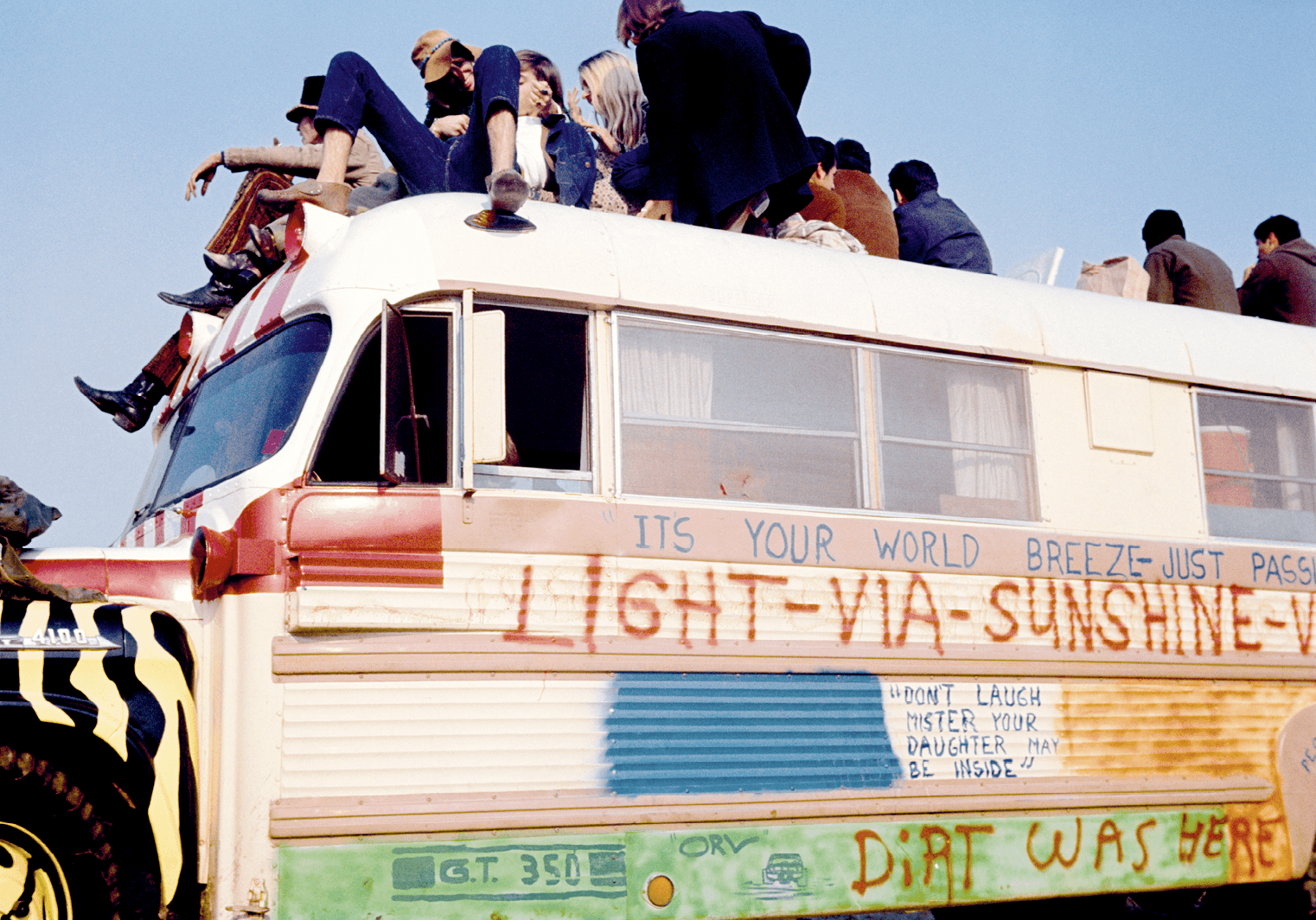 A group of hippies sit on top of a graffi ti-painted bus during Altamont free rock concert, 1969.