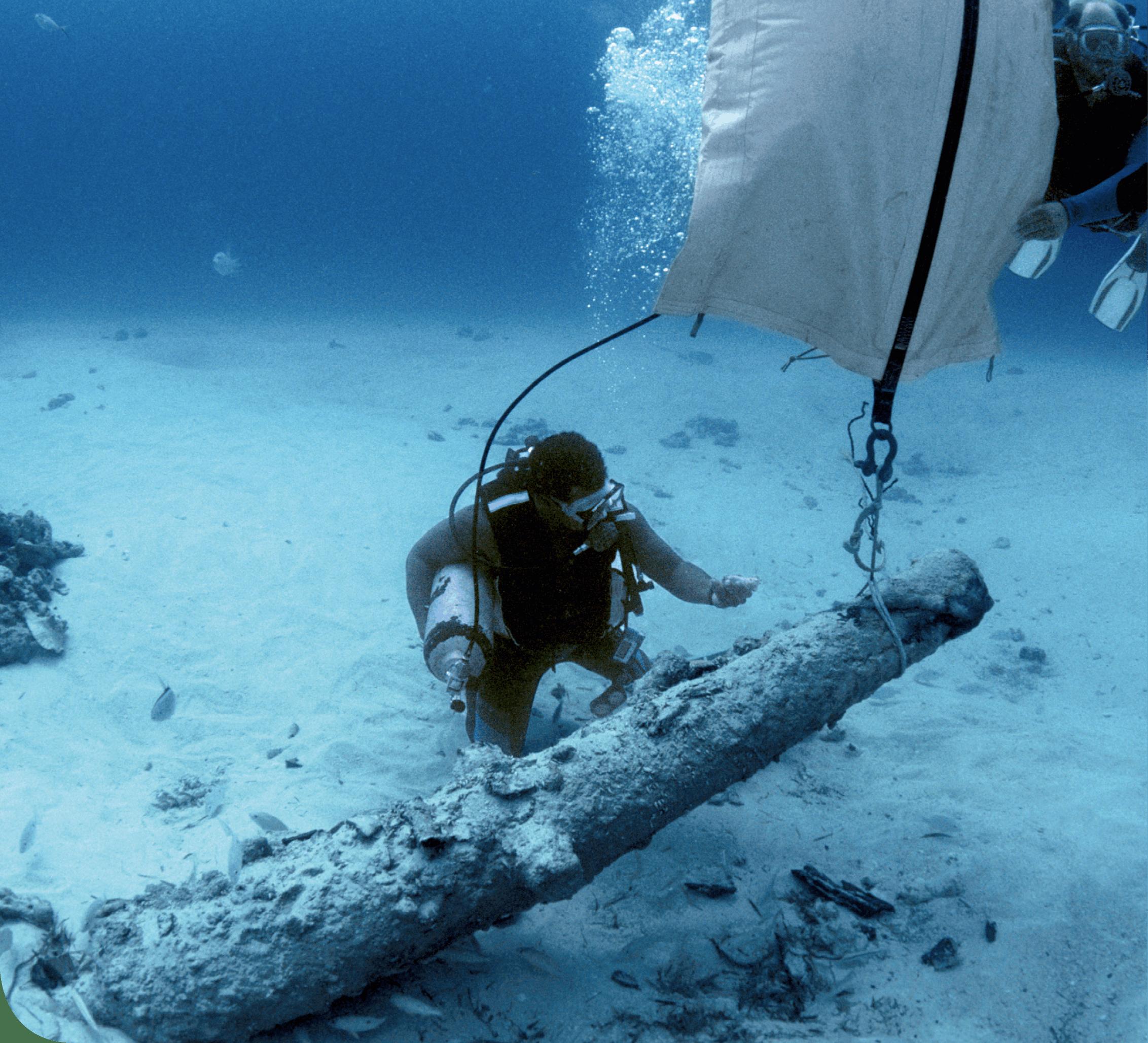 Plongeur découvrant une épave de canon de deux siècles.