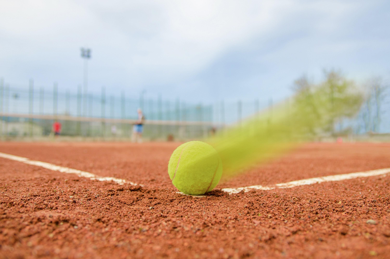 <stamp theme='pc-green1'>Doc. 1</stamp> Balle de tennis sur terre battue.