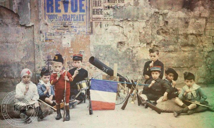 Léon Gimpel, Les enfants et la guerre : les troupes prennent un repos bien gagné tout en savourant les sucres d'orge distribués par l'opérateur, 1915, autochrome, Société Française de Photographie.