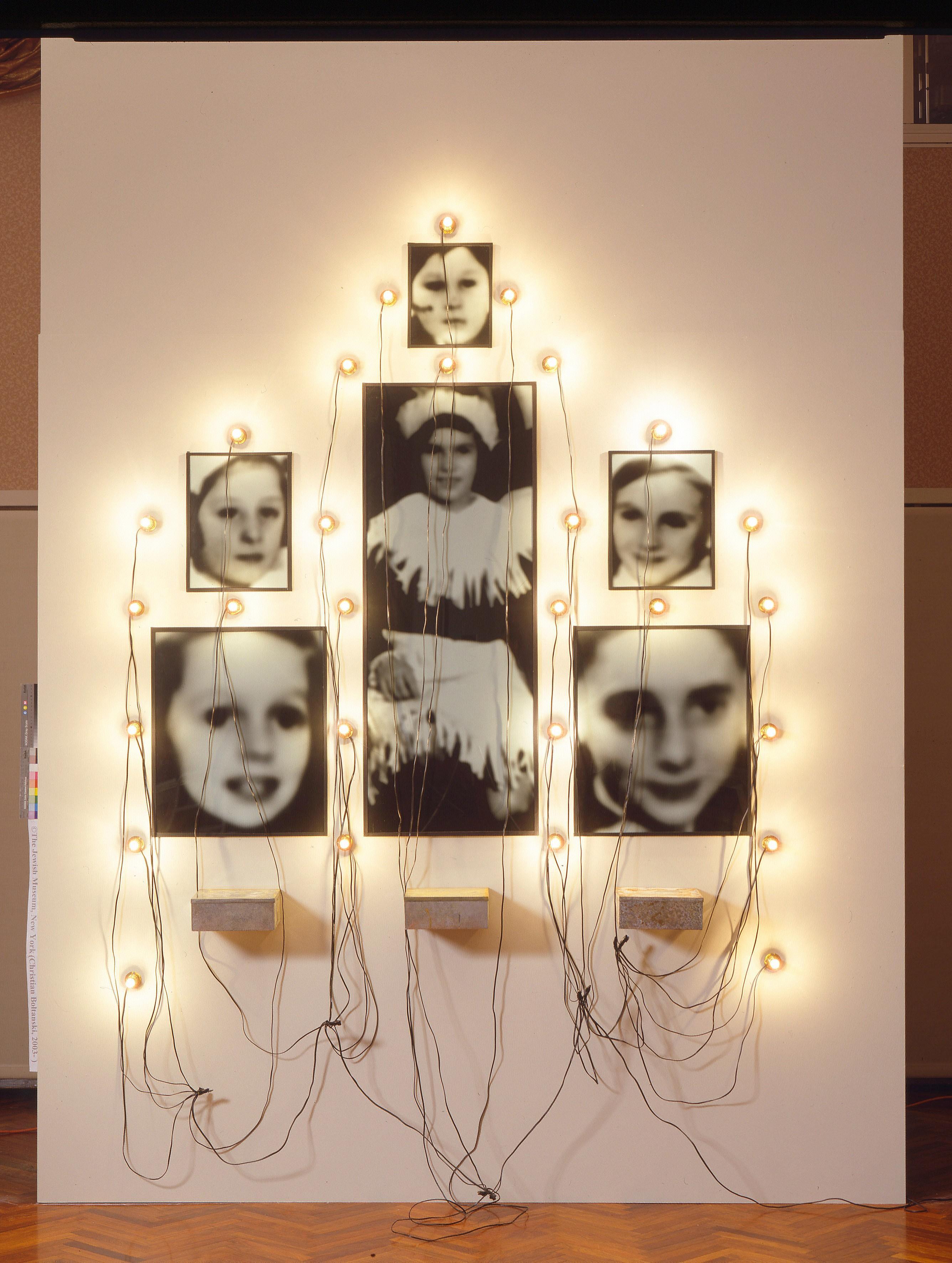 Christian Boltanski, Monument Odessa, 1989, installation : photographies noir et blanc et trois boîtes à biscuits, lampes et fils, 203,2 × 182,9 cm, Marian Goodman Gallery, New York.