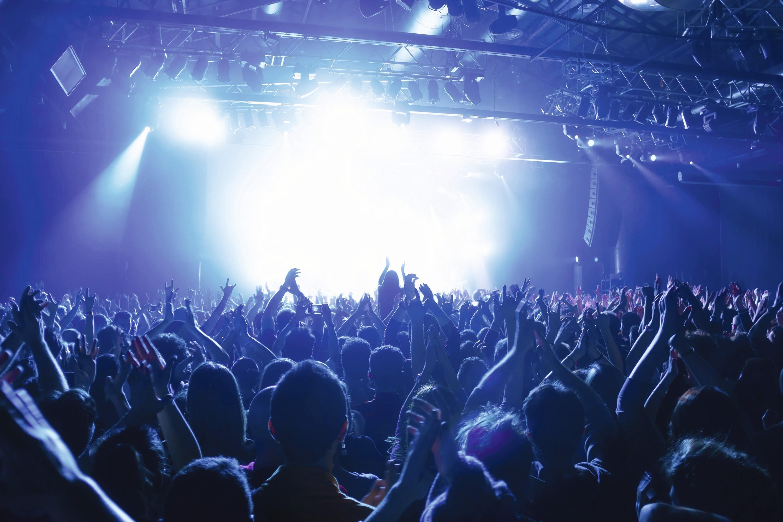Une foule devant la scène et des spectateurs plus éloignés lors d'un concert.