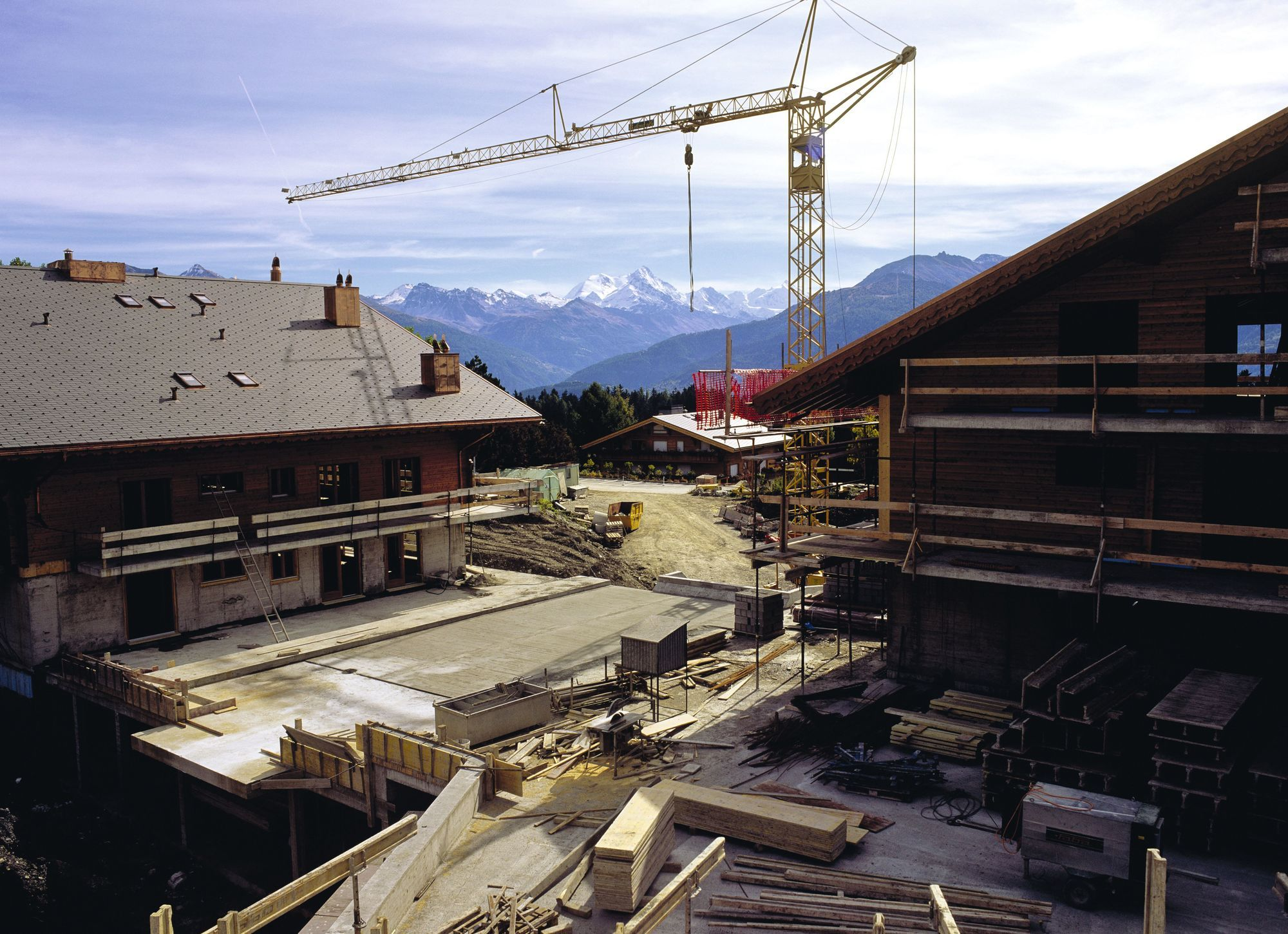Construction d'un village de vacances dans les Alpes suisses. Cela implique d'acheminer des matériaux et de créer des réseaux d'électricité, d'adduction d'eau, de traitement des eaux usées et des déchets