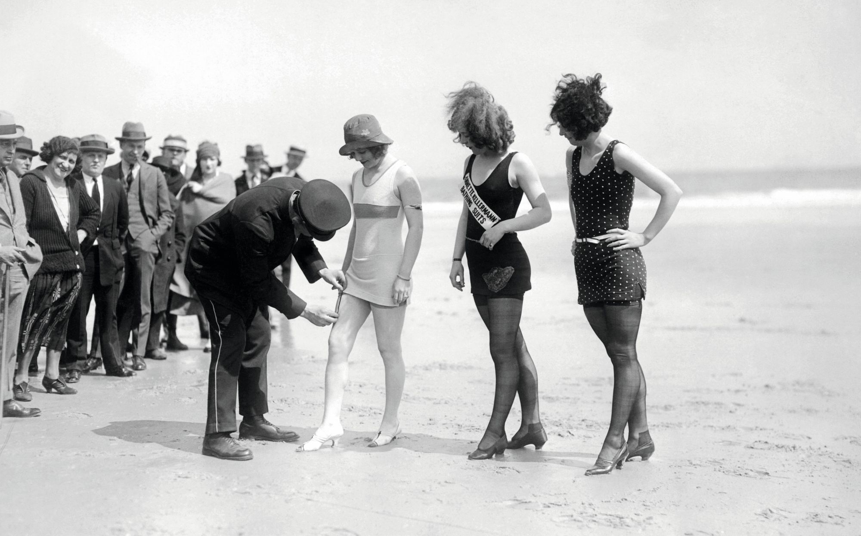 En 1921, à Atlantic City, un policier mesure la longueur des maillots de bain pour s'assurer qu'ils sont décents.